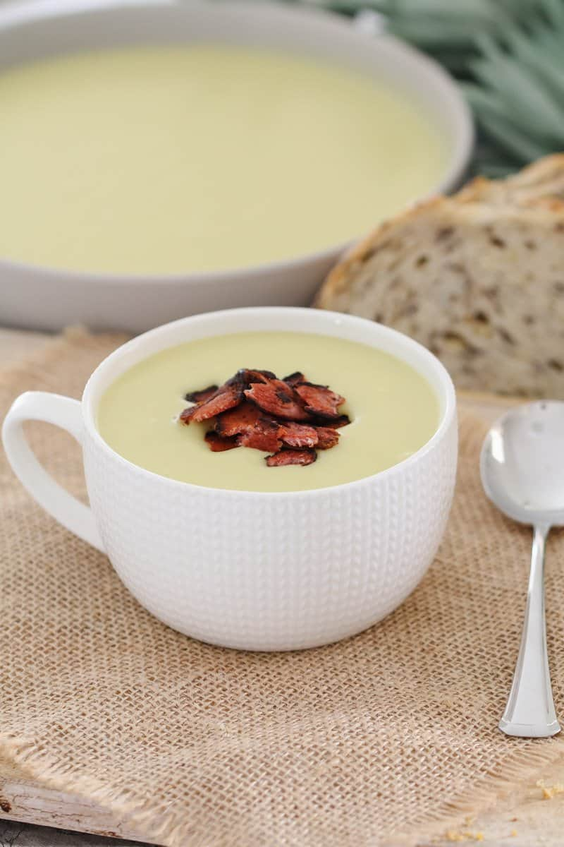 A bowl of creamy potato and leek soup with crispy bacon pieces on top.