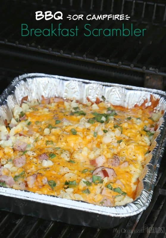 A breakfast bake of scrambled eggs, ham, spring onions and cheese being cooked in a foil tray on a camp BBQ.