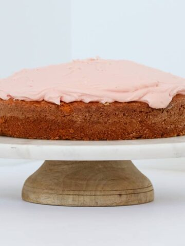 A cake with pink icing on a round cake tray