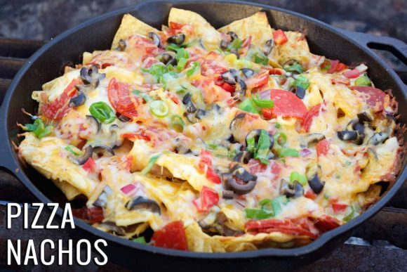 Nachos being cooked on a campfire with corn chips, chillies, olives, tomato and cheese.