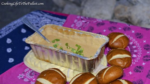 Beer cheese dip with spring onions in a foil container with bread around the outside.