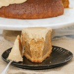 A serve of caramel mud cake on a black plate with a fork beside it, with rest of cake in the background