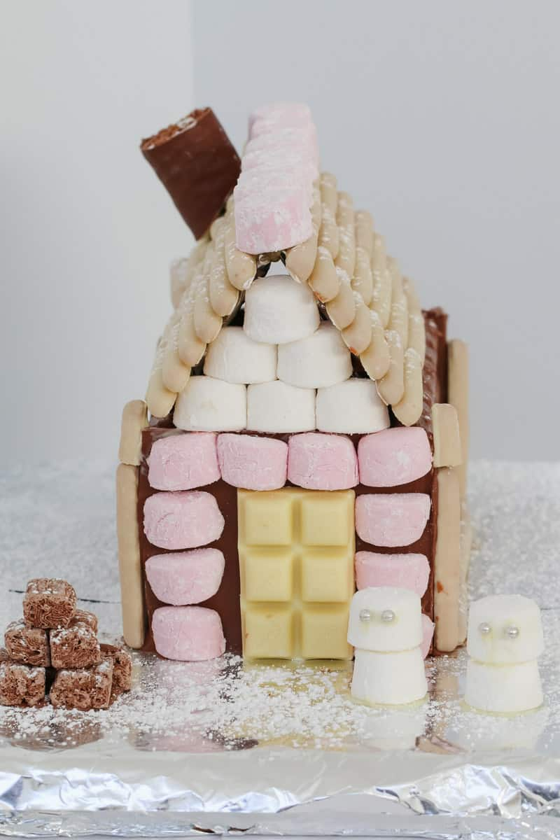A super easy Chocolate Christmas House that makes an absolute showstopper of a table centrepiece! Use your favourite chocolates to decorate!