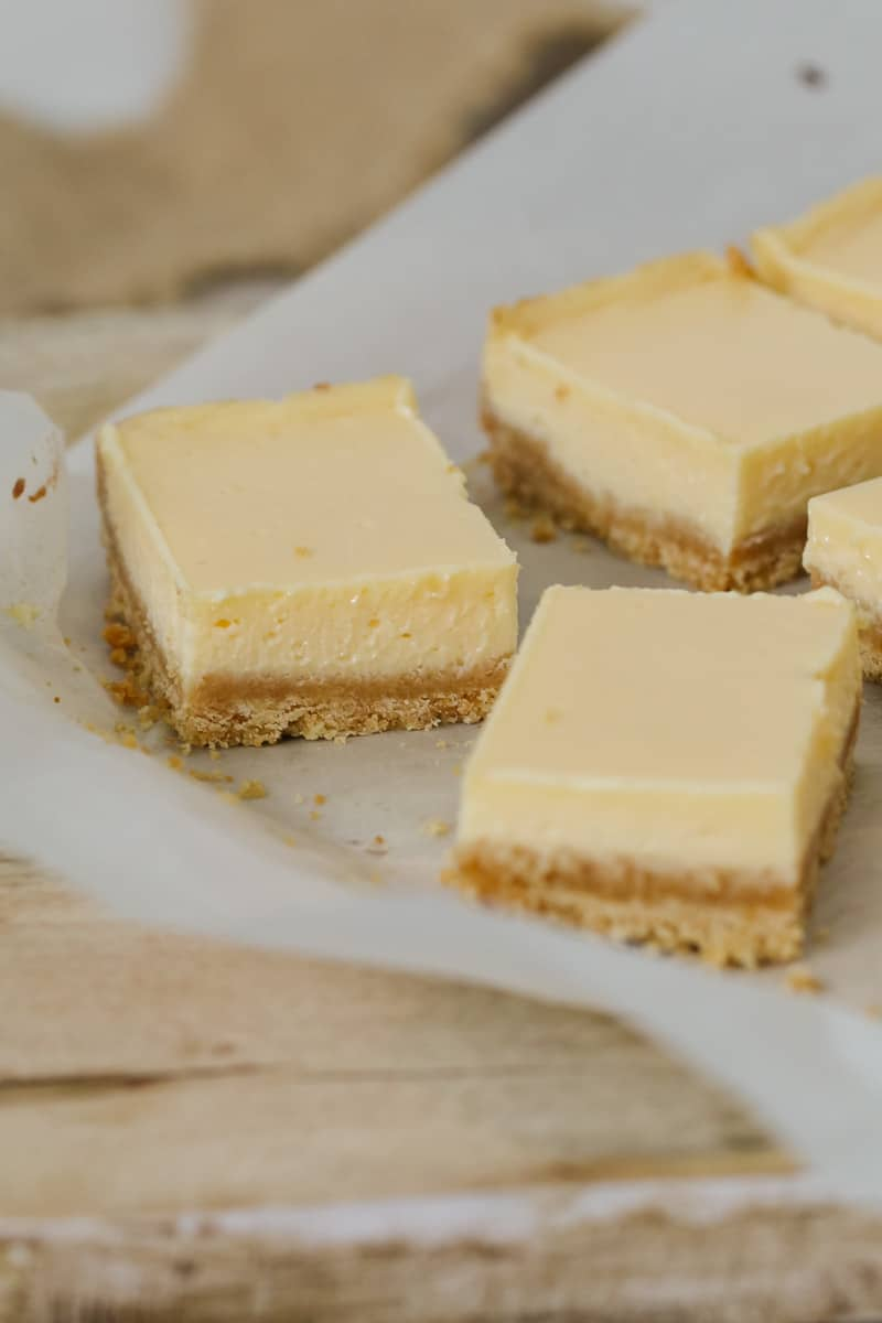Slicing a two layered creamy lemon bar into small pieces.