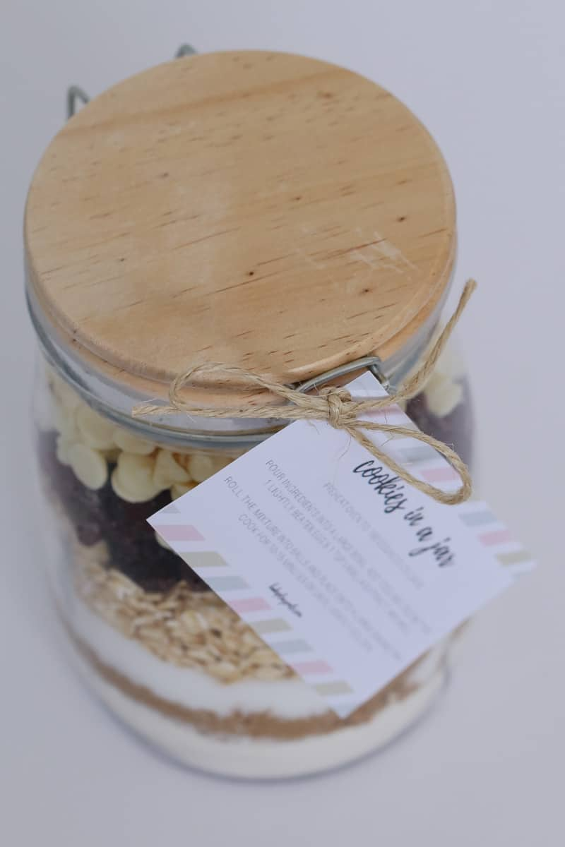Looking down at a glass lidded jar with a label attached, filled with layers of dry ingredients