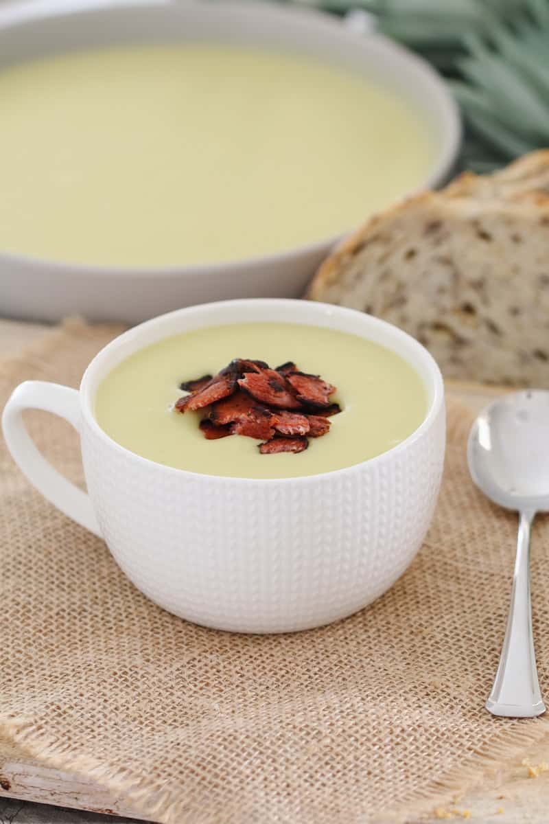 Bacon on top of a bowl of potato and leek soup.