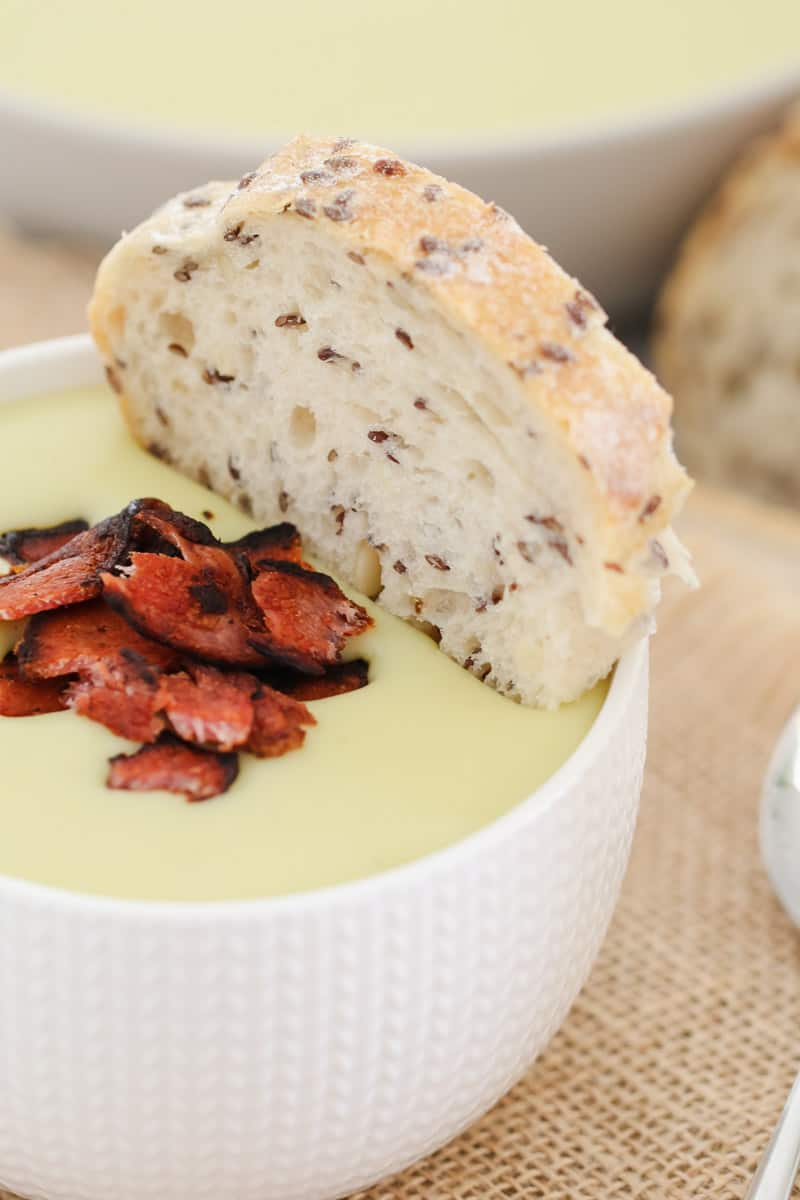 A piece of bread being dipped into a bowl of leek and potato soup with crispy bacon.