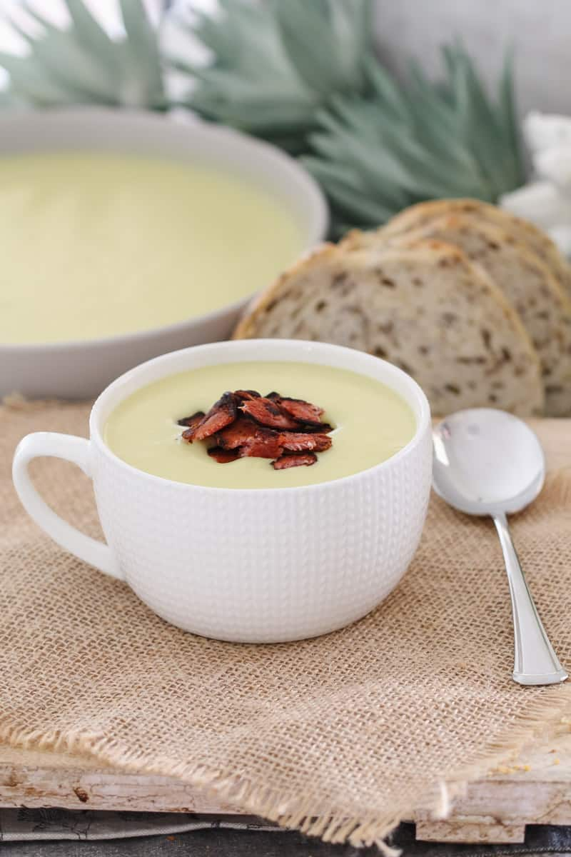 Potato and leek soup with bacon, bread slices and a large bowl of soup in the background.