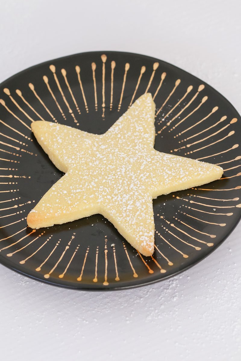 A shortbread star on a black and gold plate sprinkled with icing sugar.