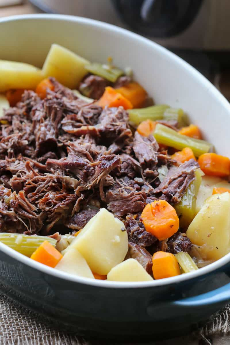 Lots of vegetables surrounding slow cooker roast beef.