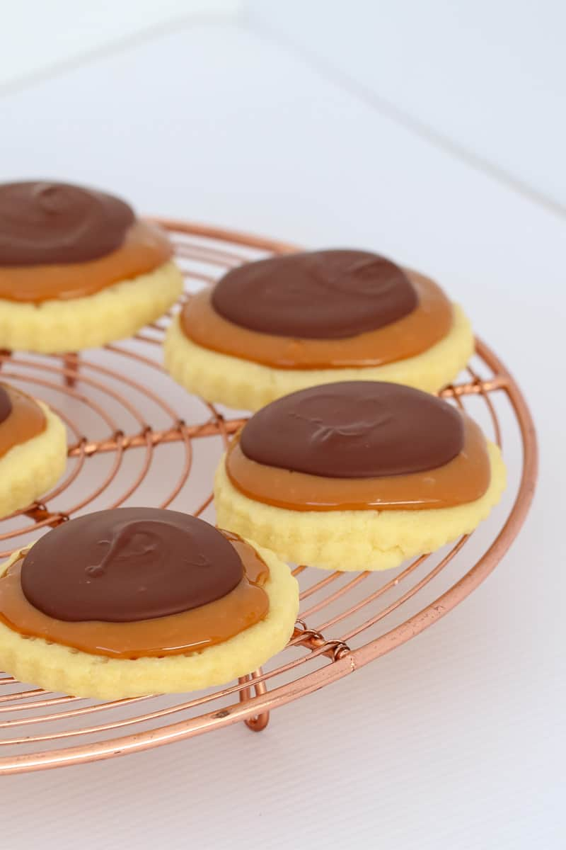 Cookies topped with caramel and chocolate on a copper wire stand