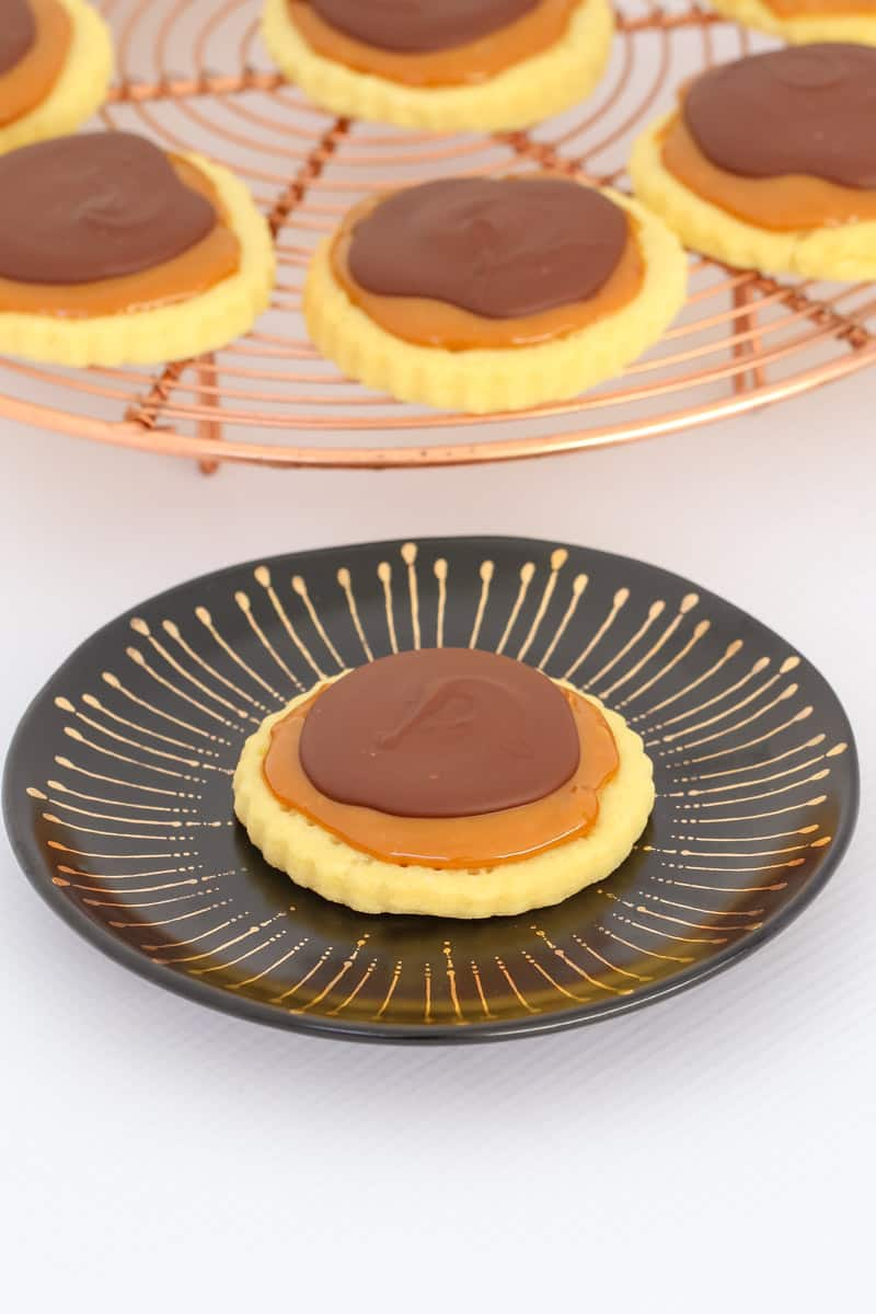 A cookie topped with caramel and chocolate on a black plate, in front of a copper wire stand with more cookies
