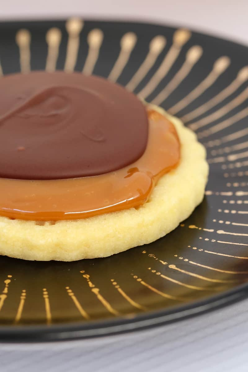 A close up of a shortbread cookie topped with caramel and chocolate on a black plate