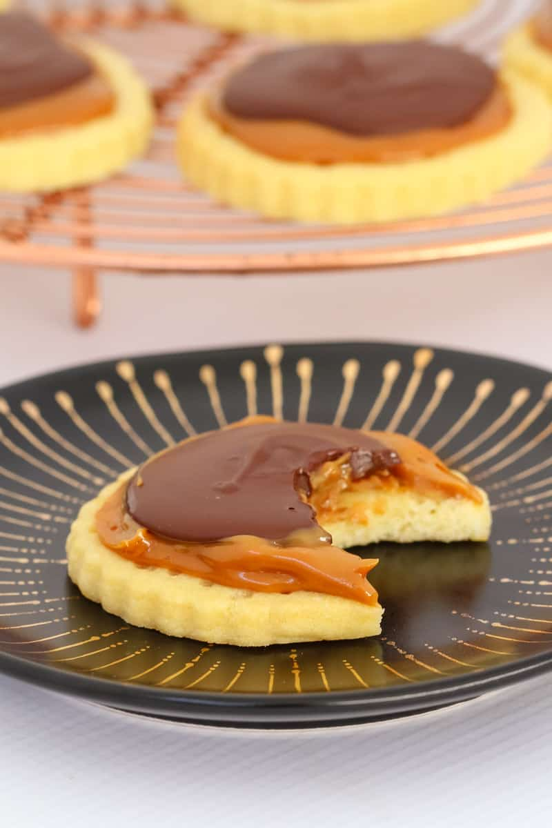 A half eaten cookie topped with caramel and chocolate on a black plate