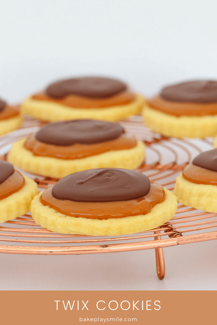 Shortbread cookies topped with caramel and chocolate on a copper wire stand.