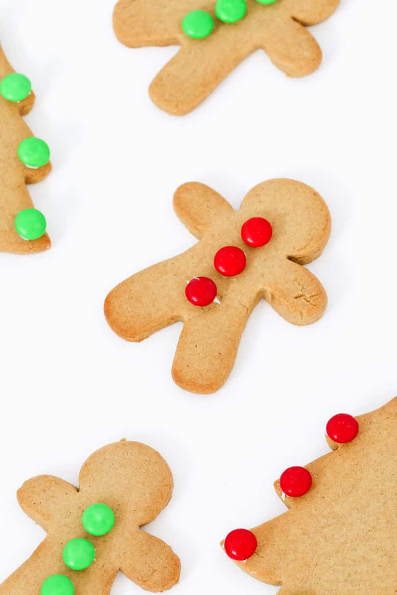 Homemade gingerbread men with red and green decorations.