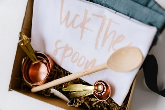 A classic cooking hamper with a linen apron, copper measuring cups and spoons, a wooden spoon and designer tea towel.