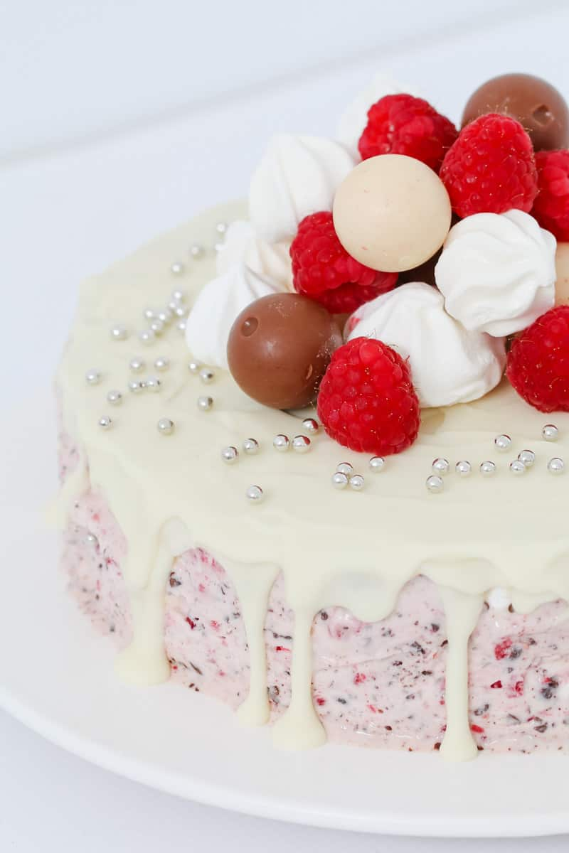 A close up of a round cake drizzled with white chocolate and decorated with raspberries and lollies