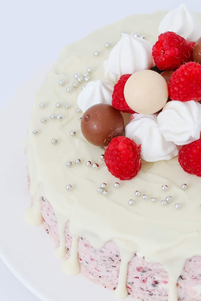 A close up of a raspberry ice cream cake decorated with raspberries and sweets