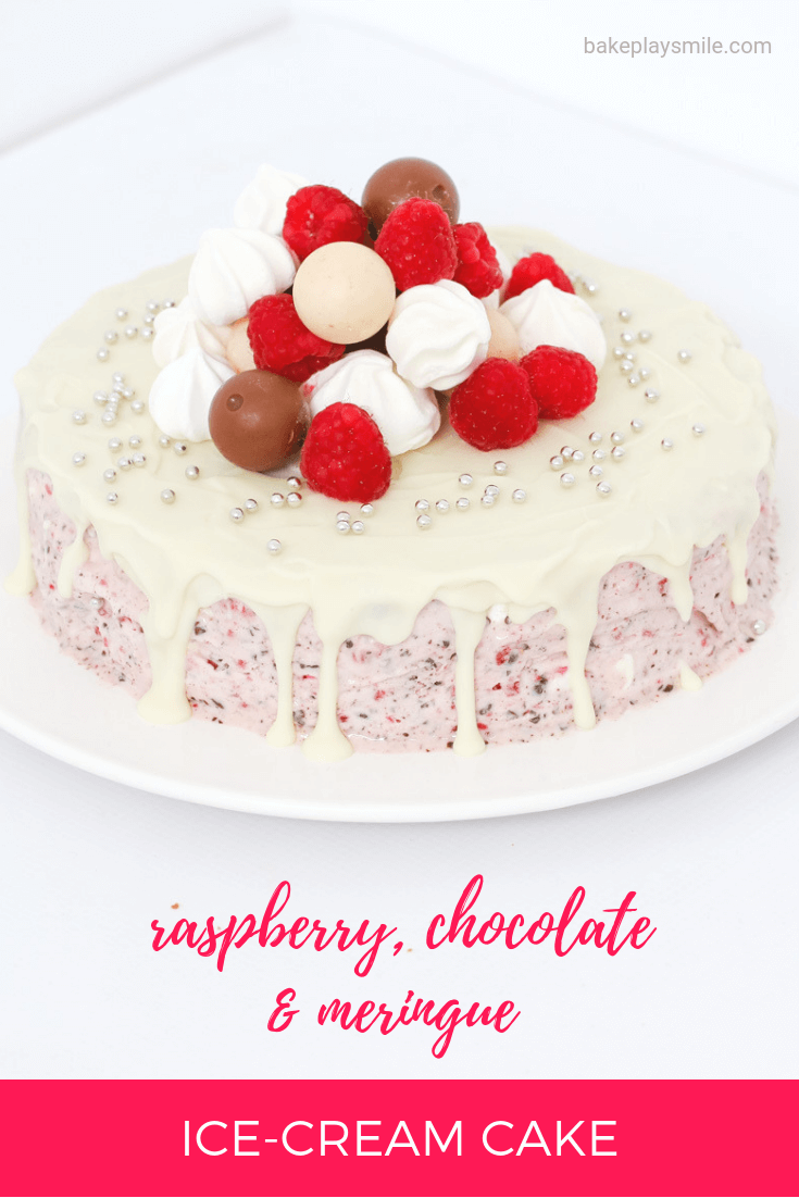 A round cake drizzled with white icing and decorated with raspberries and lollies