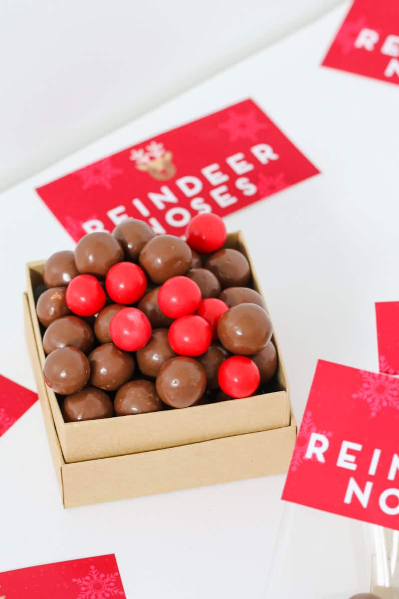 A container filled with malted milk balls and red chocolate balls with reindeer nose labels in the background.