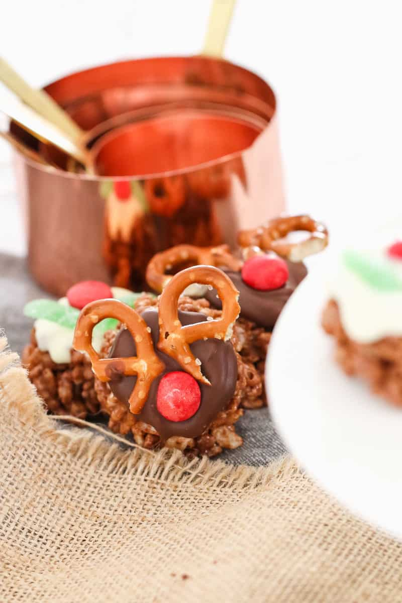 Chocolate crackles decorated with pretzels and red lollies in front of a copper measuring cup