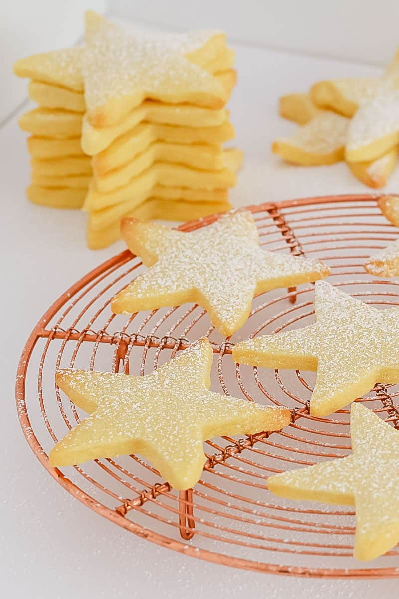 Star shaped shortbread on a round copper wire tray, with a stack of shortbread in the background