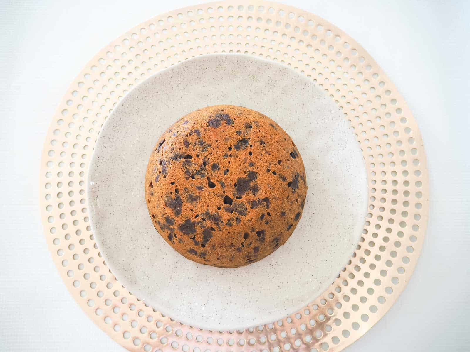Looking down on a round Christmas pudding on a pink and white plate