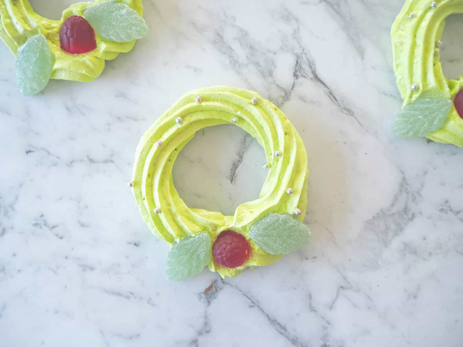 Mini meringue wreaths decorated with lollies on a marble board.