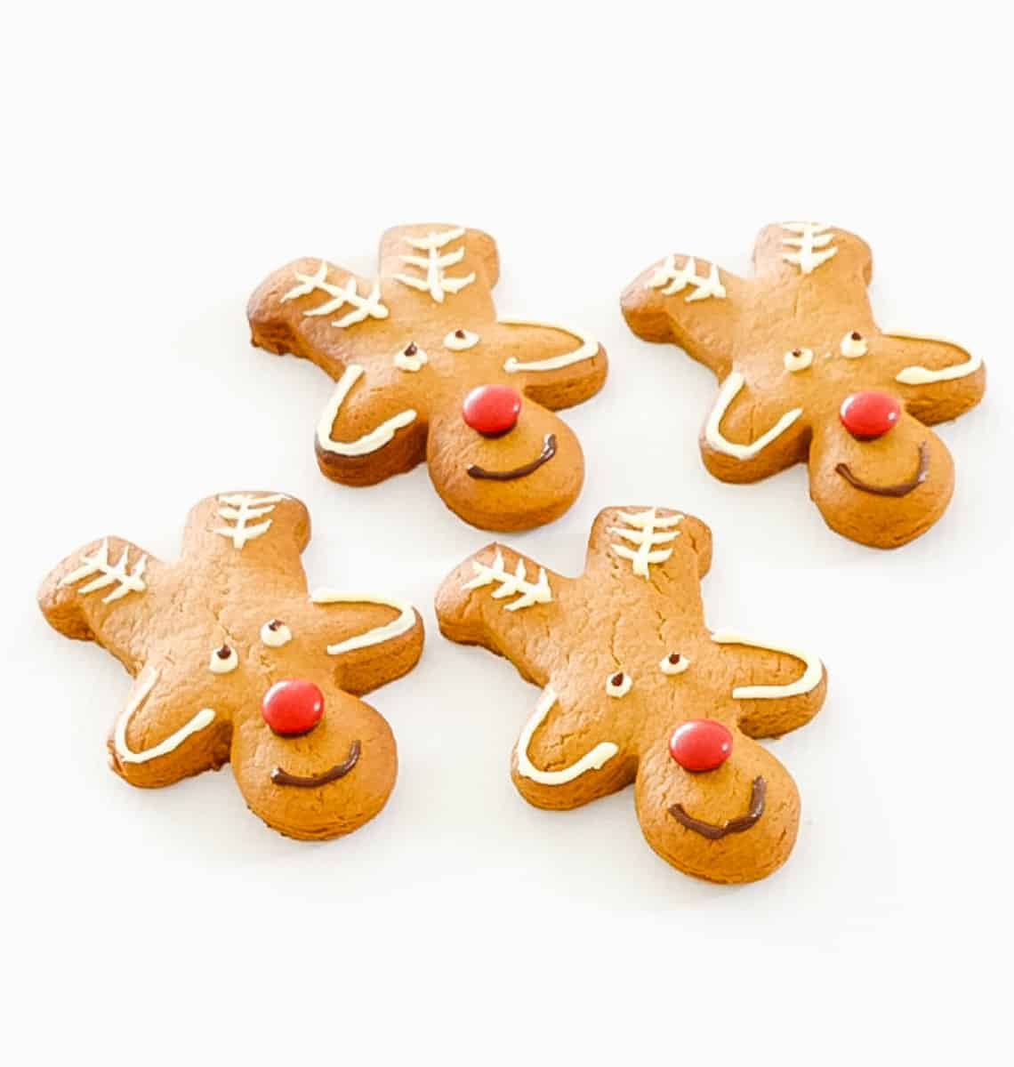 Biscuits shaped and decorated with icing and lollies to make reindeer faces