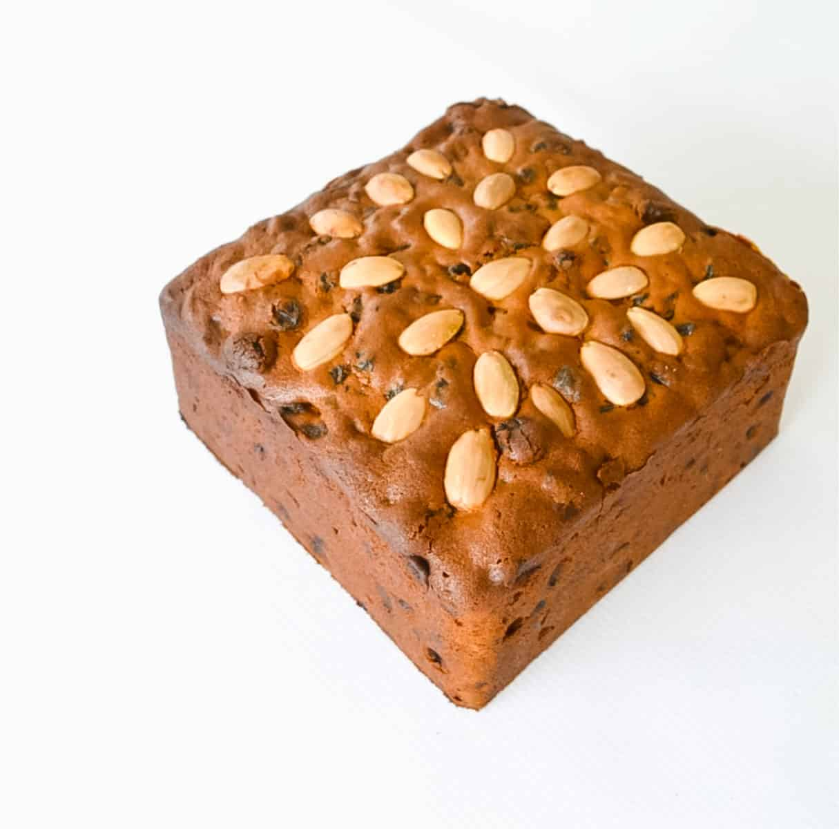 A square Christmas cake decorated with almonds on top