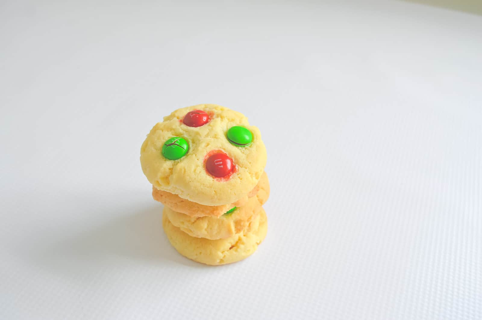 A stack of biscuits decorated with red and green Smarties