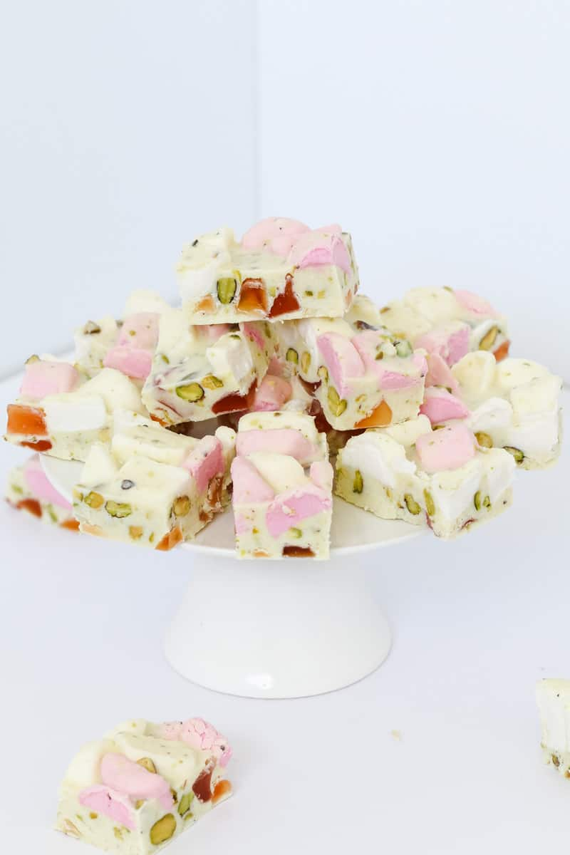 A white cake stand with a stack of white chocolate Rocky Road filled with marshmallows, turkish delight and pistachios
