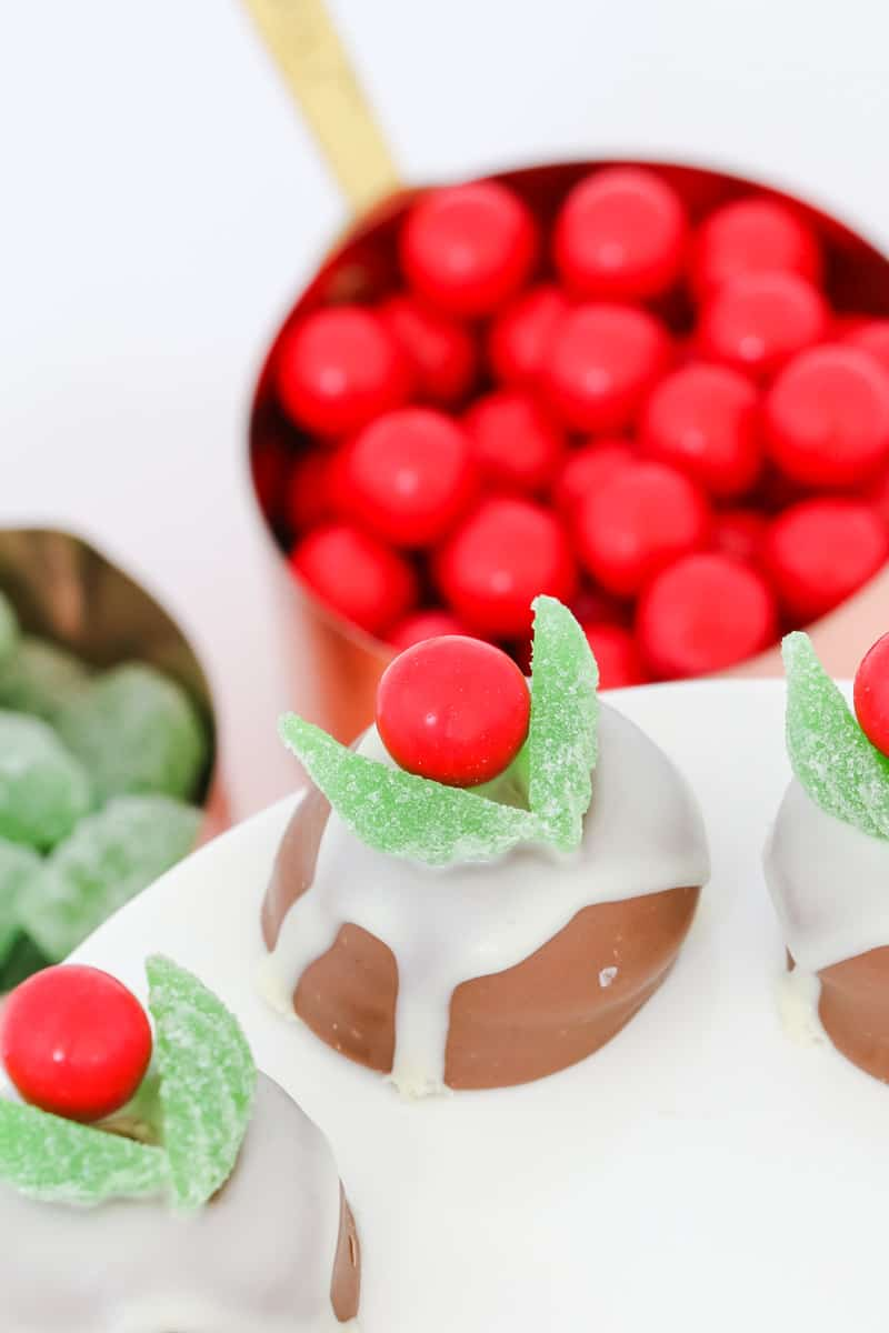 Chocolate Christmas puddings made from chocolate marshmallow biscuits, melted white chocolate, jaffas and spearmint leaves on a white plate.