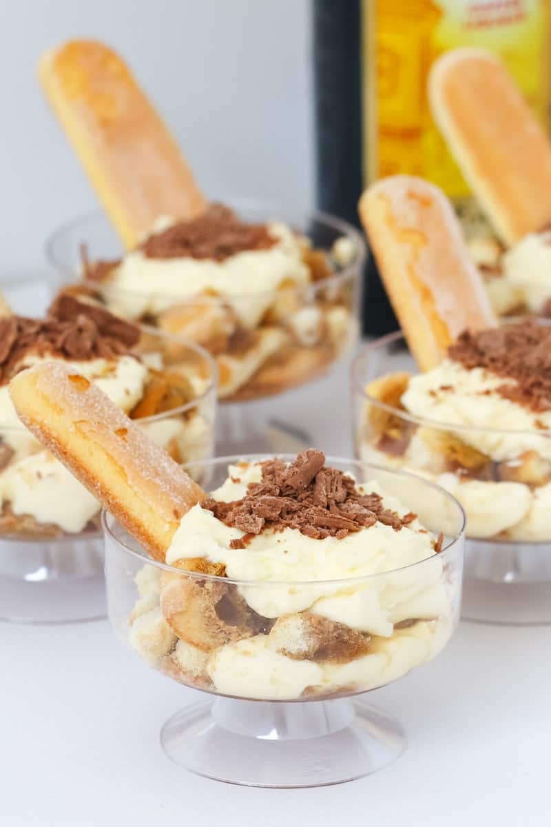 Four mini Kahlua tiramisu's in glass dessert bowls.