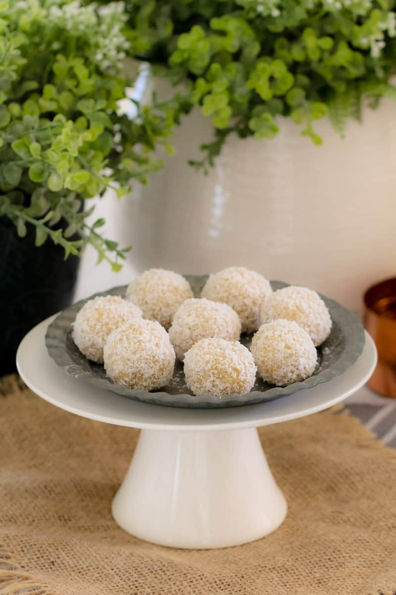 Eight balls rolled in desiccated coconut on a plate atop a white cake stand.