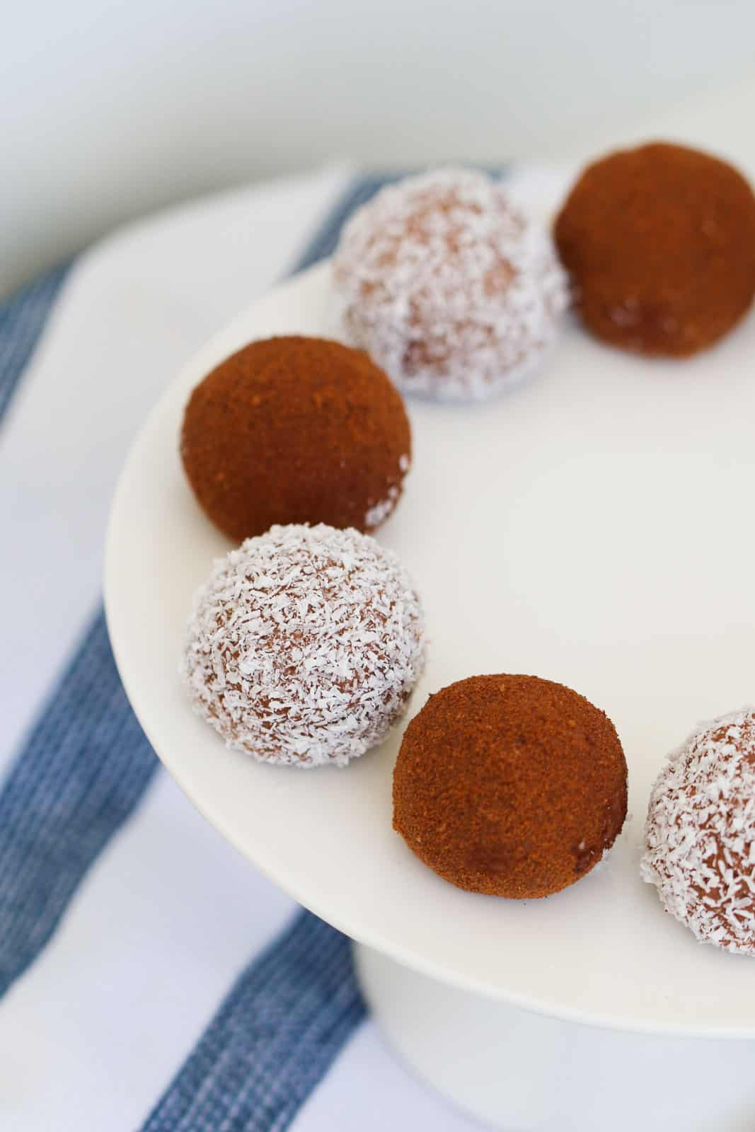 Coconut and cocoa balls on a white cake plate.