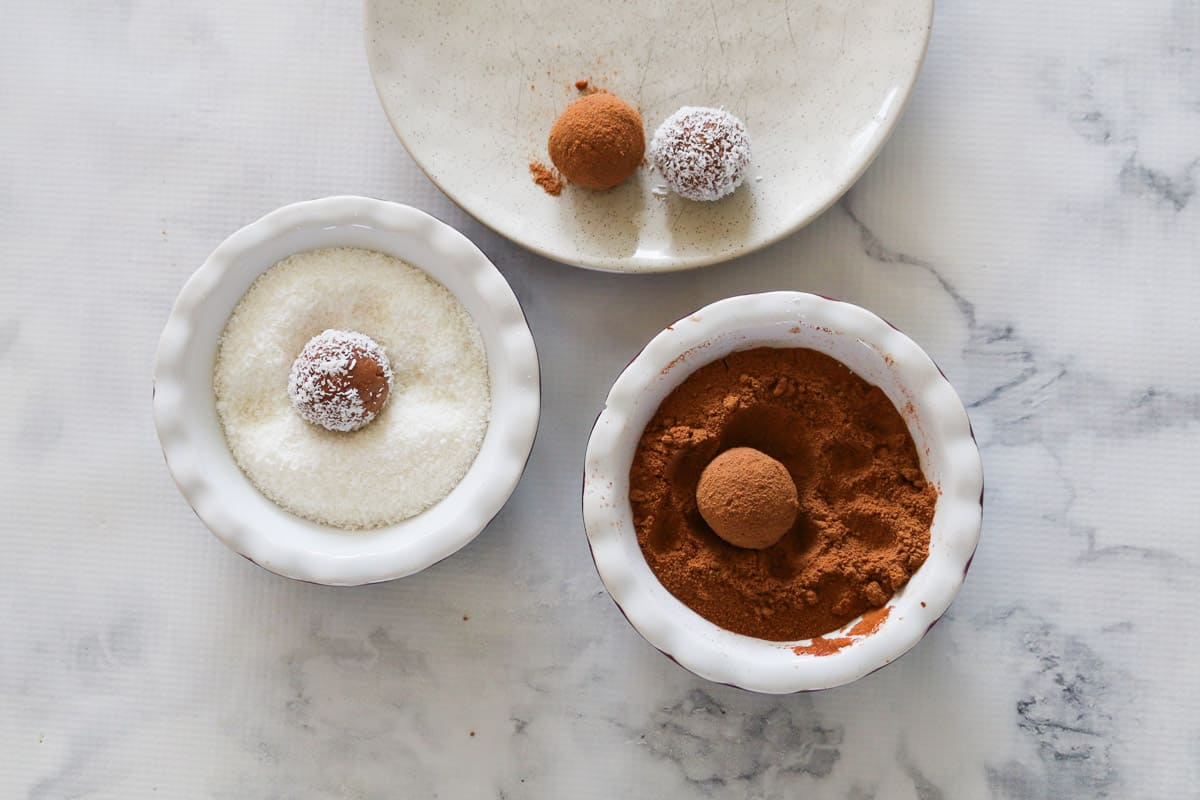 Chocolate balls being coated in bowls of coconut and Milo.