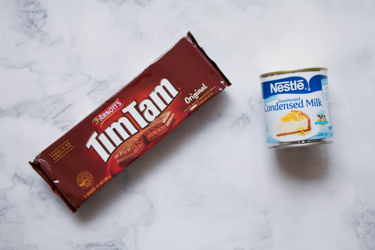 A packet of chocolate Tim Tam biscuits and a tin of sweetened condensed milk.