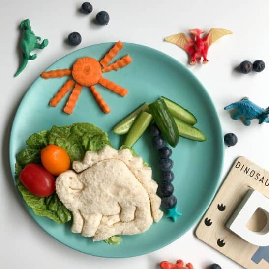 A dinosaur shaped sandwich on a plate. A fun kids lunch.