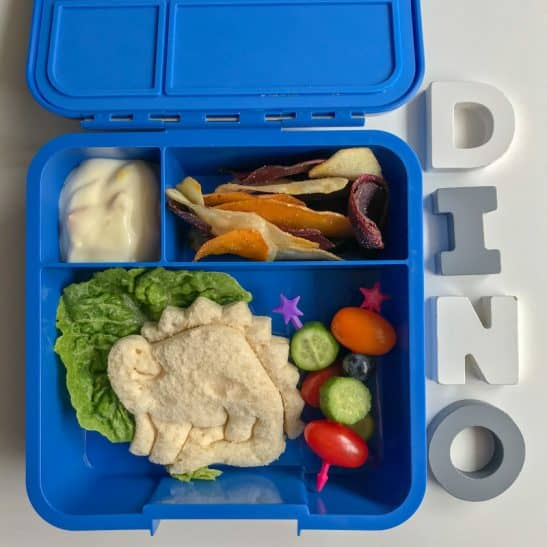 A bento style lunch box with a dinosaur shaped sandwich.