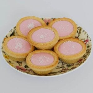 Six tarts with pink icing on a floral plate