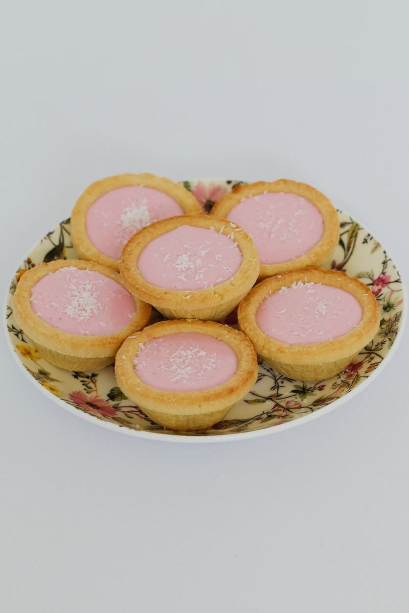 A plate of marshmallow tarts with coconut.