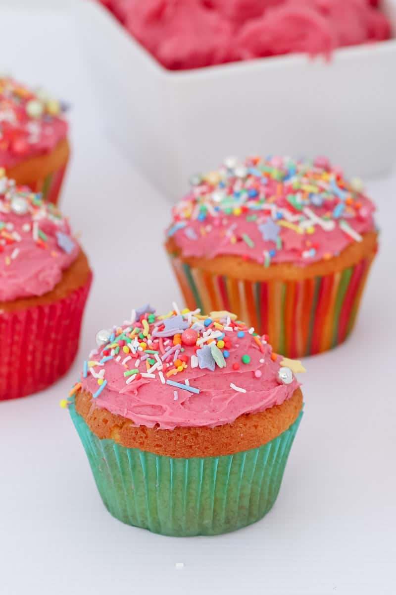 Vanilla cupcakes with sprinkles on top.