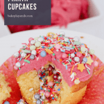 Piñata cupcakes with sprinkles coming out from the middle and pink frosting on top.
