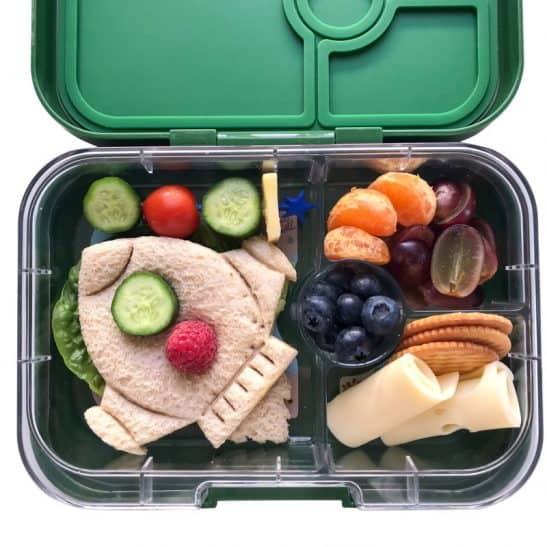 A kids school lunchbox filled with healthy food and a rocket shaped sandwich.
