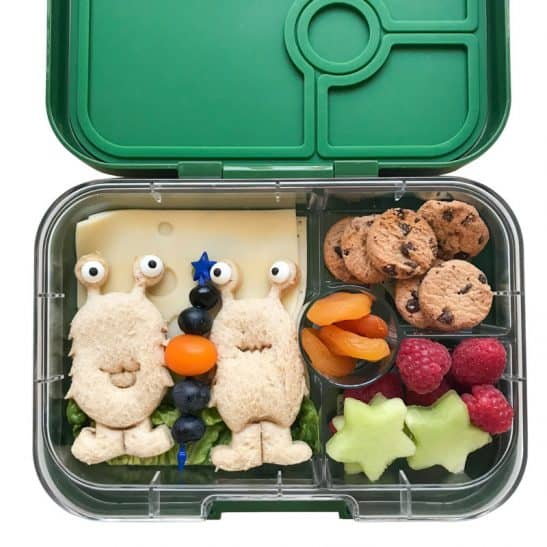 A bento school lunchbox with alien shaped sandwiches and star shaped fruit.