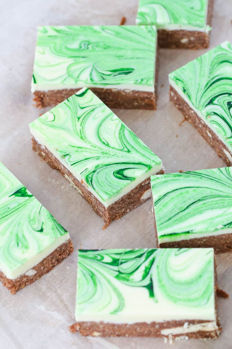 Green food colouring swirled through white chocolate on top of a peppermint slice.