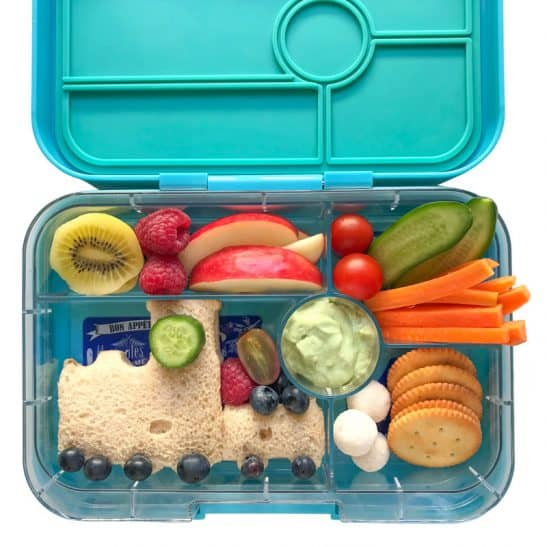 A school lunchbox filled with healthy food and a train shaped sandwich.