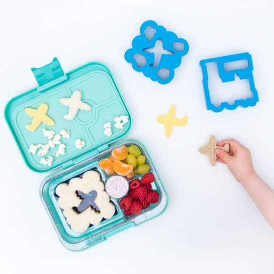 A lunch box with fruit and a cloud shaped sandwich with a small plane.